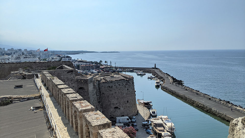 Northern wall and moat with Turkish and Northern Cyprus flags over Girne Castle